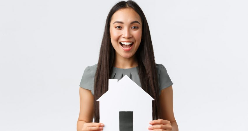 Insurance, loan, real estate and family concept. Cheerful asian female buying or selling home, holding paper house and smiling upbeat, searching for new apartment, white background.